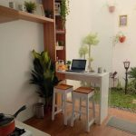 Small Kitchen With Wooden Floor, White Small Island With Wooden Stools, Wooden Shelves ,tiny Patch Of Garden