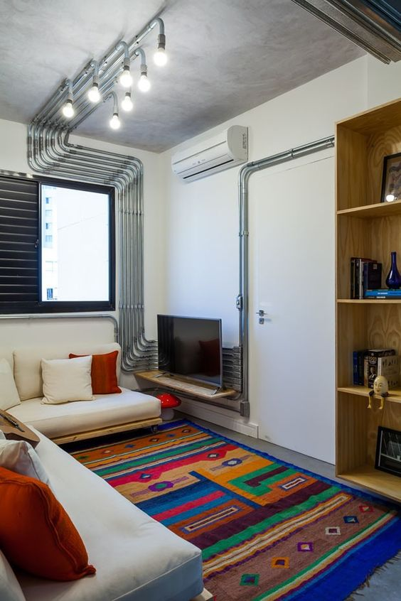 small living room, TV on small woodene floating shelves, white wall, white cushioned wooden bench with wheels, colorful rug, shelves