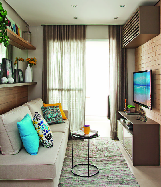 small living room, beige floor, grey rug, off white sofa, open brcik wall with TV, brown cabinet, floating shelves
