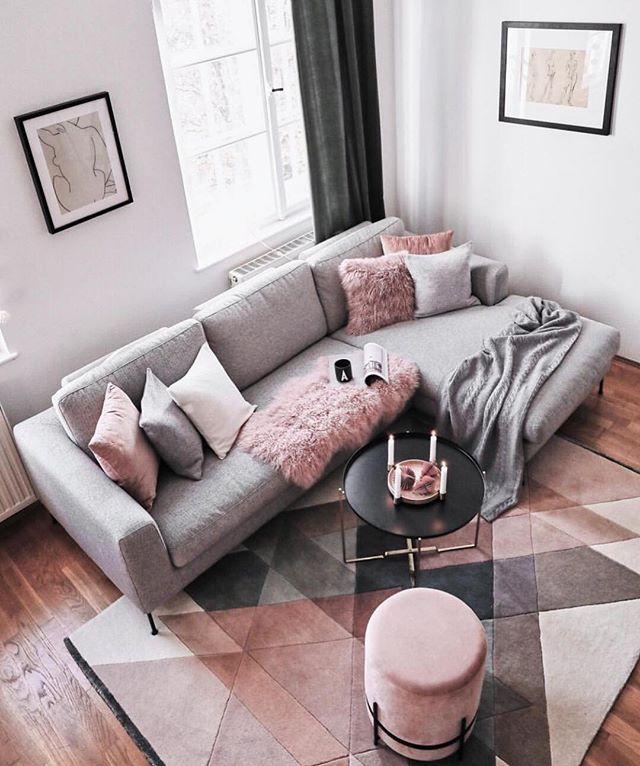 small living room, wooden floor, grey corner sofa, round pink otoman, black coffee table, pink geometric rug, white wall