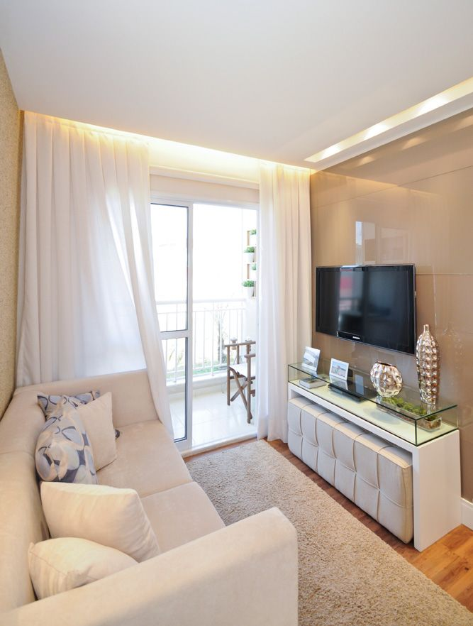 small living room, wooden floor, rug, white wooden console table with glass box top, white bench under table, white sofa, white curtain, glass sliding door