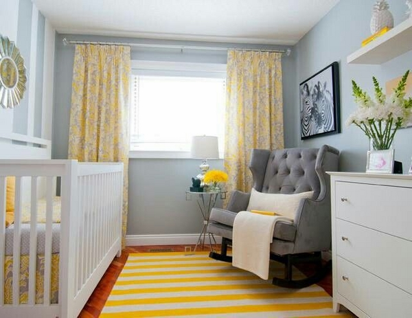 small nursery, white cot, chest of drawers, gray armchair, bright area rug