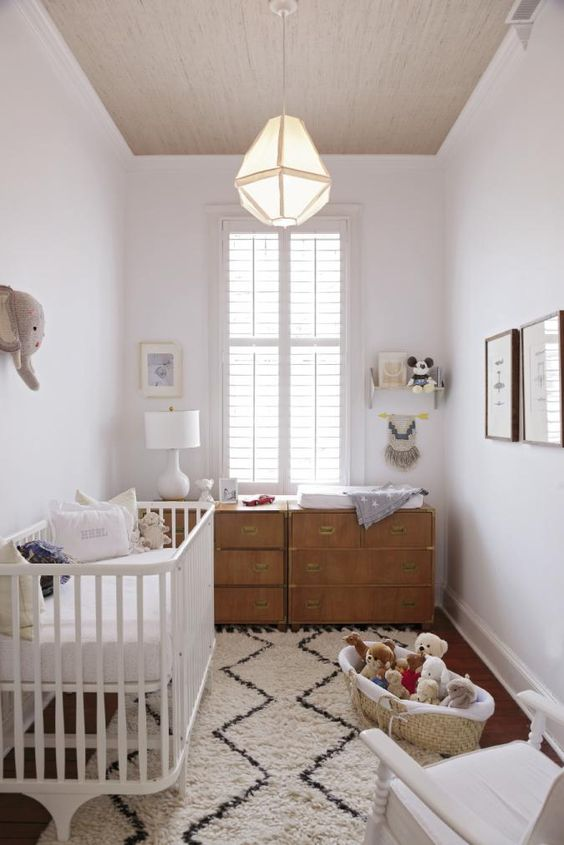 small nursery, wooden floor, white rug, white wall, wooden ceiling, white cot, wooden drawers, cabinets, white wooden rocking chair