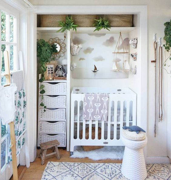 small nursery, wooden floor, white rug, white wooden cot, white built in cupboard, white baskets, white stool, white wooden rack