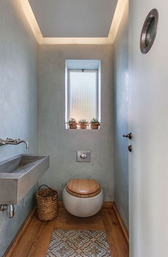 small powder room, greyish blue wall, LED ceiling, wooden floor, white toilet with wooden cover, grey sink