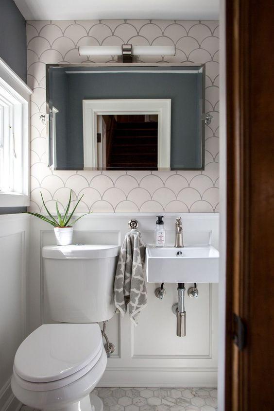 small powder room, white wainscoting, white hexagon floor tiles, grey wall, fish skin accent, white toilet, shite sink, mirror, white LED