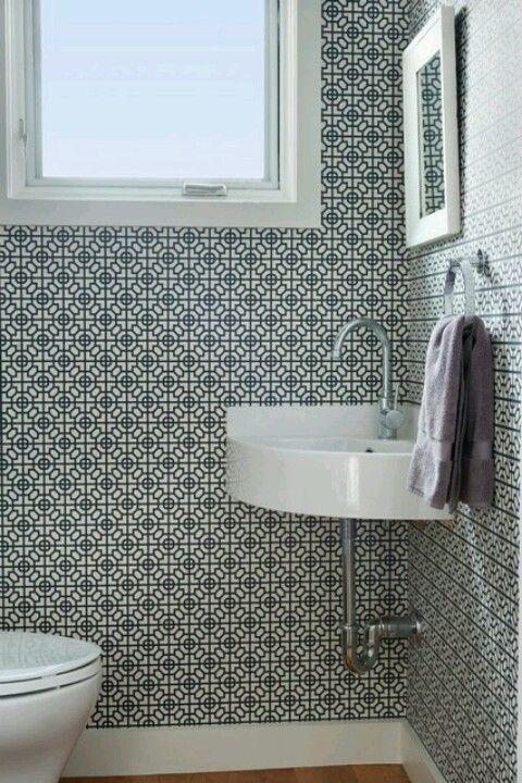 small powder room, wooden floor, tiny geomteric patterned wallpaper, white corner sink, white framed small mirror, white toilet