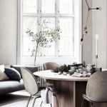 Small Round Dining Table With Grey Velvet Chairs, Wooden Floor, White Wall, Glass Window, Grey Sofa