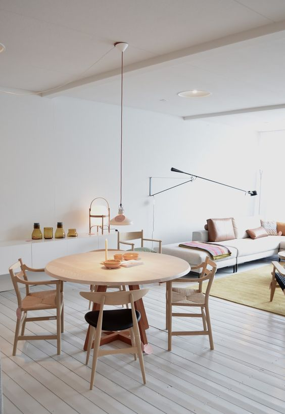 small round wooden dining set with wooden chairs on a room with grey floor, white cabinet, white sofa, white wall, long pendant