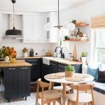 Small Round Wooden Table With Wooden Chars, Rattan Rug, Bench On The Window Sill, Kitchen With Dark Cabinet Wnd Wooden Top, Pendant