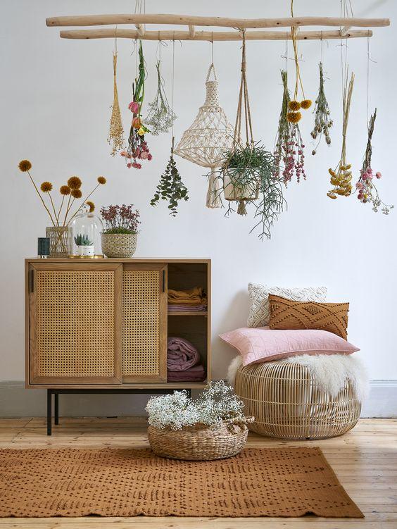 small wooden cabinet with rattan sliding door, wooden floor, rattan ottoman, brown rug, pillows,