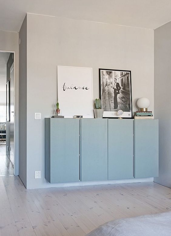 soft blue floating ivar cabinet on off white wall, wooden floor