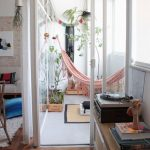 Soft Pink Hammock On Balcony, White Floor, White Wall, Large Window, Plants On Square Wooden Pot