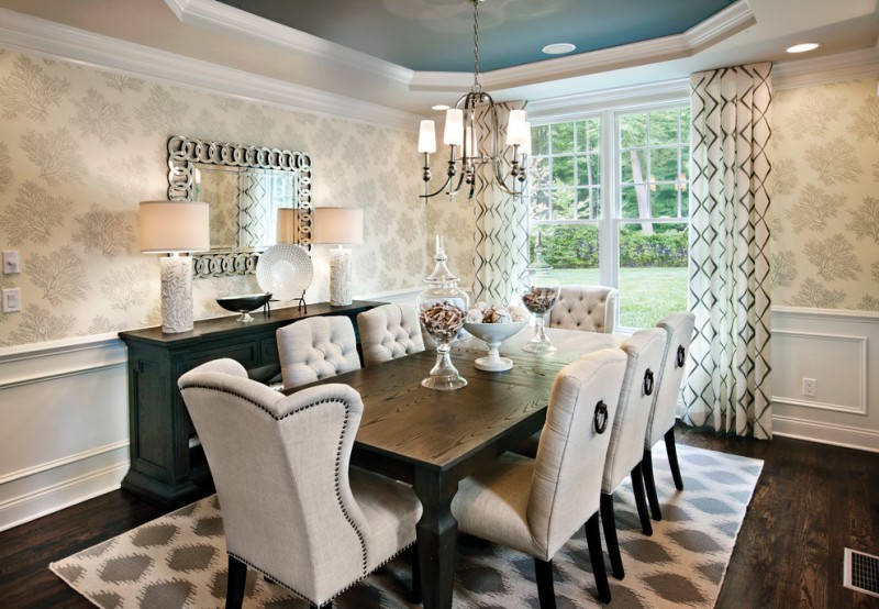 studded dining chair patterned area rug dark wood flooring wall mirror glass windows white curtains wooden dining table chandelier table lamps