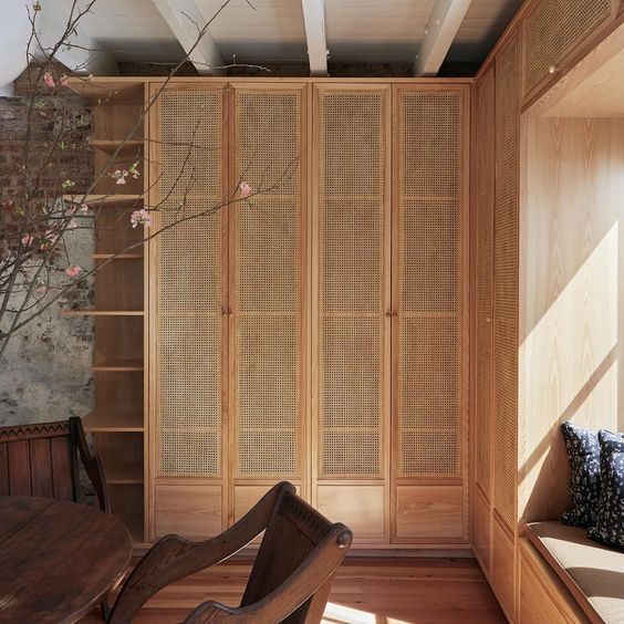 tall built in wooden rattan cupboard, wooden window nook, wooden shelves, wooden floor, wooden table and chair