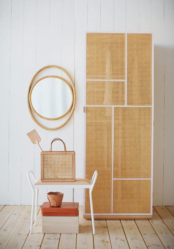 tall rattan cupboard with white lines, wooden floor, mirror, stool