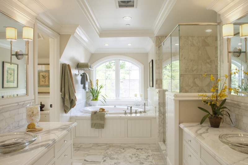 towel rack height glass windows built in tub wall sconces double vanity white marble countertops glass shower doors granite floor and wall tiles