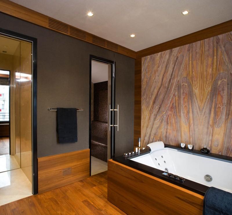 tub deck accent wall wooden floor tile grey walls towel holder glass shower doors jaccuzi built in tub black shower deck tub filler
