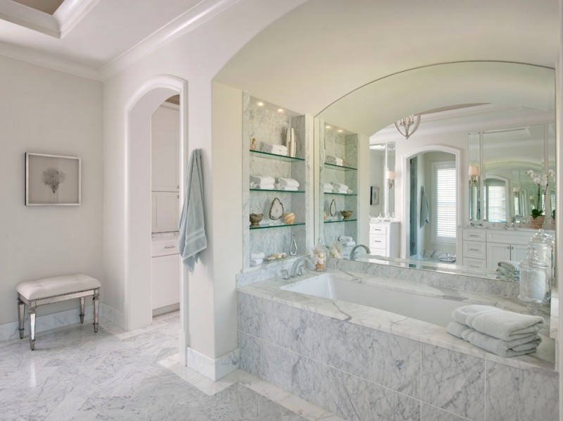 tub deck built in glass shelves grey marble tiles large wall mirror faucet chandelier white bench towels windows artwork white walls