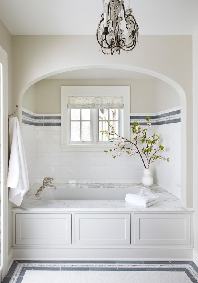 tub deck chandelier white and grey wall and floor tiles built in tub towel holder indoor plant small glass window window shade