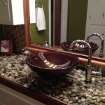 Vanity With Pebbles On The Surface, Enclosed With Glass, Brown Sink, Silver Faucet, White Cabinet, Mirror