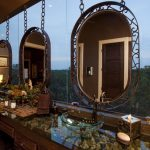 Vanity With Pebbles On The Table, With Glass Surface, Clear Sink, Framed Mirror, Wooden Cabinet