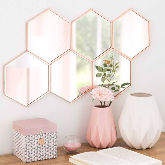 wall mirror with honeycomb pink framed on white wall, pink vase, white vase