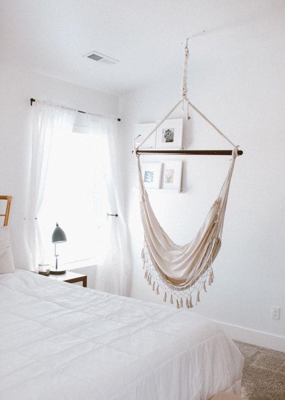 white bedroom, rug floor, white bedding, white wall, white ceiling, white curtain, side table, table lamp, hammock swinging chair