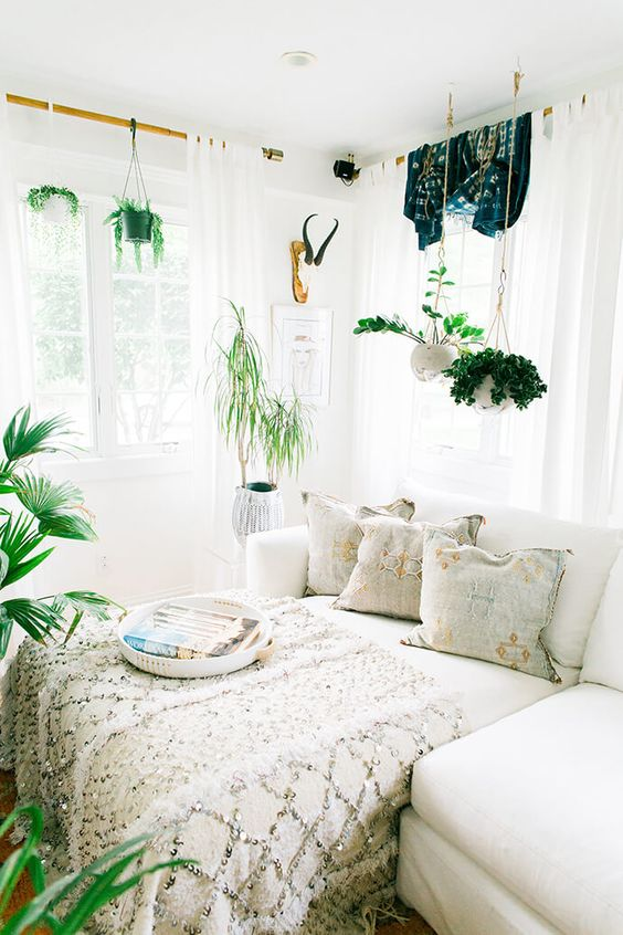 white boho bedroom with white pull out bed, white wall, white curtain, green plants, white wall, white ceiling