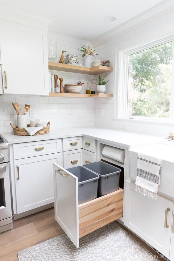 white drawers with two trash bin, drawers abinets under white top, white wall tiles, wooden floating shelves