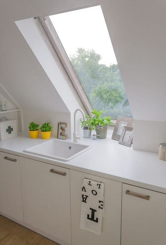 white kitchen, white sloping wall, white cabinet, white kitchen top, wooden floor