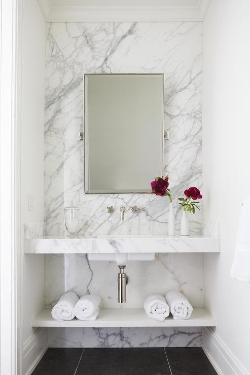 white marble floating vanity, white sink, white wooden shelves under, white marble accent wall, white wall, mirror, black floor