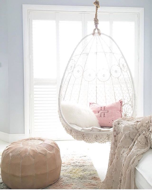 white patterned woven bedroom swing with pillows, white rug, leather ottoman, white bedding, white floor, blue wall, wooden windows