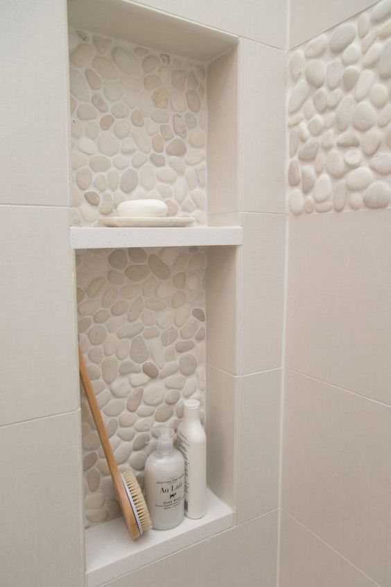 white pebbles on shampoo niches, whiet wall tiles