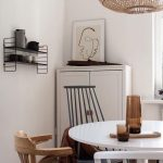 White Round Dining Table With Several Chairs, Wooden Floor, Rattan Covered Pendant, White Wall, White Cabinet