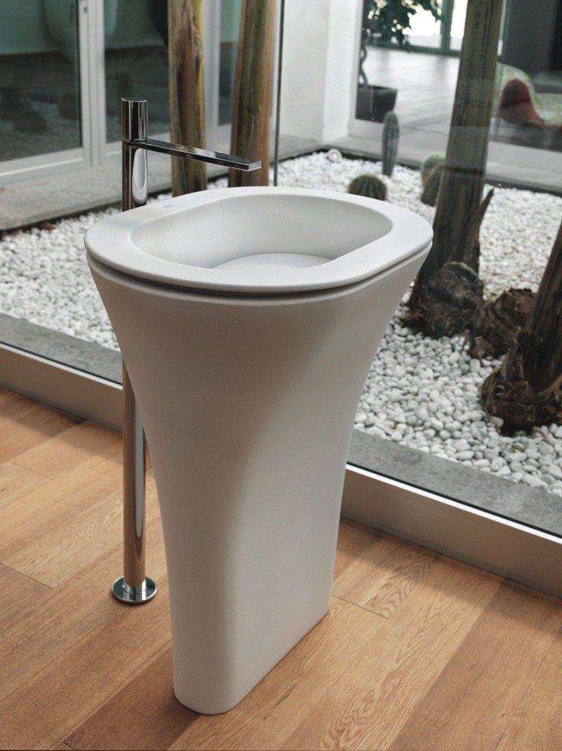 white round sink with flatter shaped on the bottom part, silver faucet