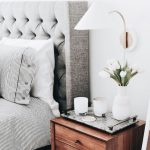 White Tulip Covered Bedside Sconce, White Wall, Wooden Bedside Cabinet, Grey Bedding, Grey Headboard