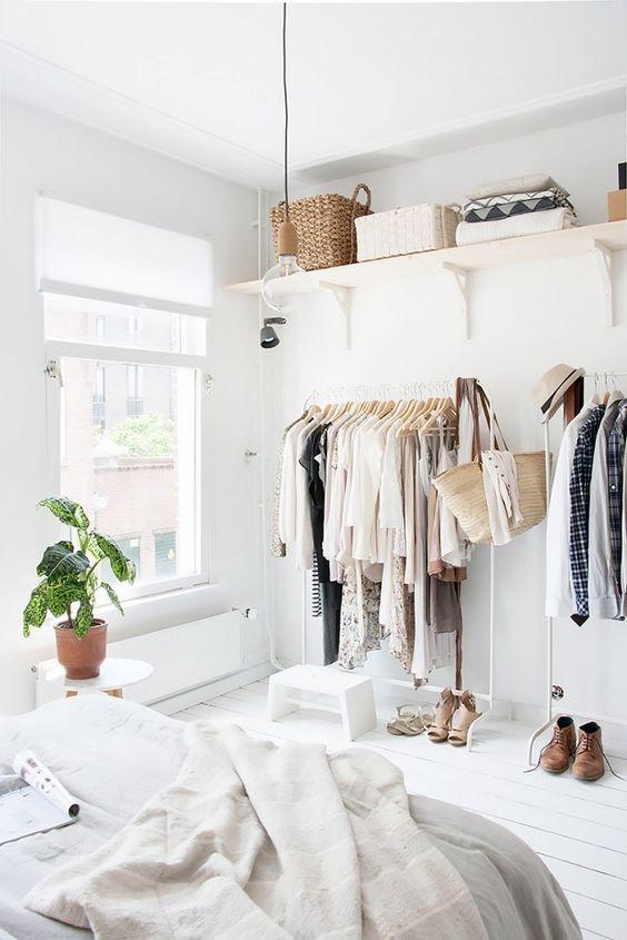 white wooden floor, white wall, white ceiling, white rails, white floating shelves, bulb pendants, white bedding, white roudn side table