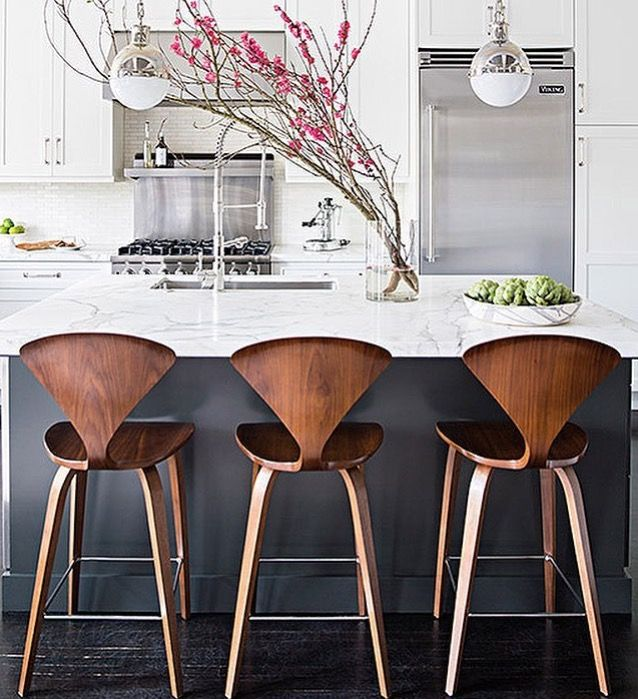 wooden bar stool with back, wooden legs, grey island with white marble top, white backsplash, white cabinet