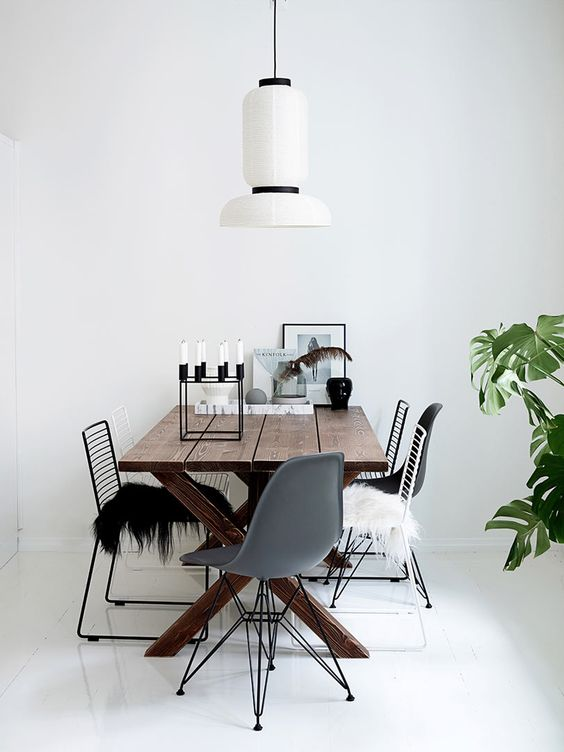 wooden dining table, mix of modern chairs, white wall, white lantern pendant, white glossy floor, plant