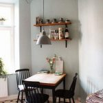 Wooden Dining Table On The Corner With Black Wooden Chairs, Light Green Wall, Floating Shelves, Pendant