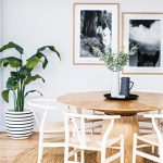 Wooden Dining Table, White Wooden Chairs With Rattan Seating, Rattan Rug, Wooden Floor, White Wall, Plant