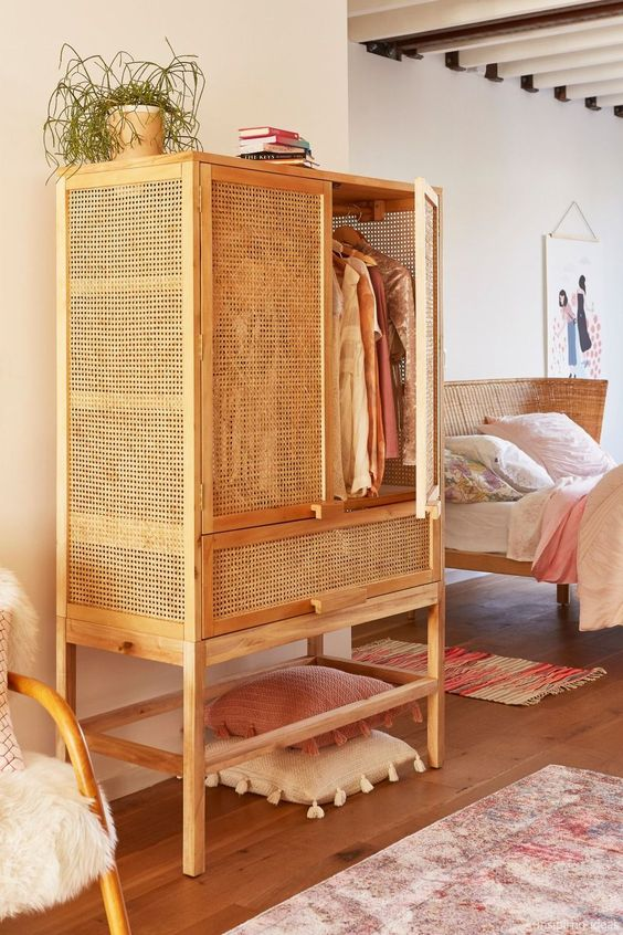 wooden rattan cupboard with drawer and tall legs, wooden floor, rug, rattan bed with white bed, pillow