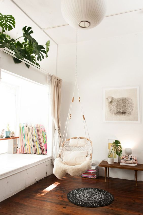 wooden rattan hanging chair with pillows and blanket, white wall, wooden floor, white reading nook on the window, wooden table, plants