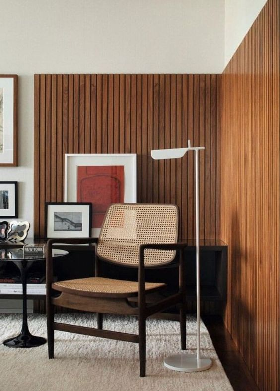 wooden slats on half bottom wall, wooden floor, rug, wooden chair, glass top side table, off white wall
