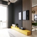 Wooden Slats On The Wall Partition Beside Black Open Brick Wall, Low Yellow Cabinet, Wooden Floor, Modern Pendants