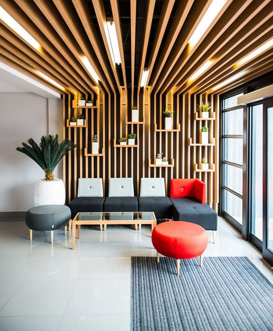 wooden slats on the wall with lights between and floating plants on the pots, gey sofa with grey red backs, grey red round ottomans, coffee table with glass top