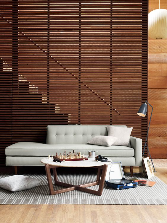 wooden slats partition between the wooden stairs and living room with wooden floor, grey rug, grey sofa, coffee table with white round top, grey floor lamp