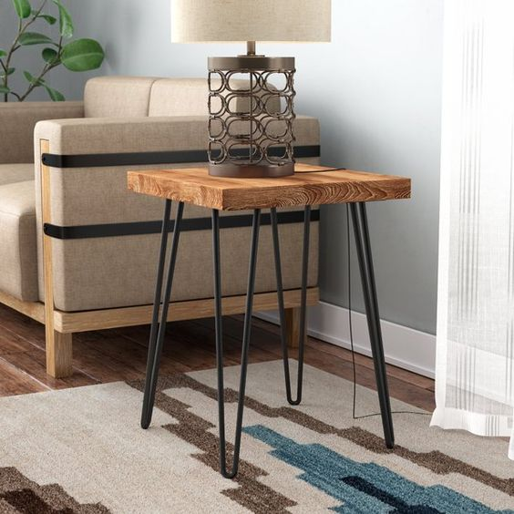 wooden square end table top with metal legs, wooden floor, rug, brown sofa, table lamp