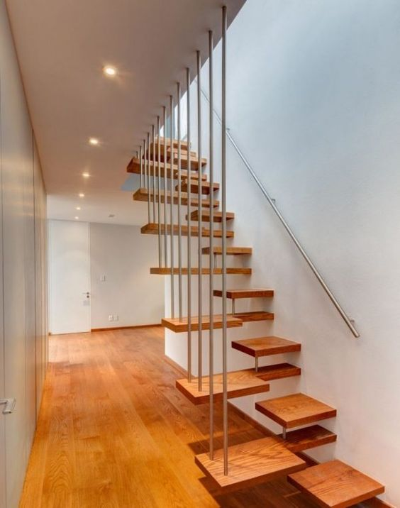 wooden stairs with half step on the right, metal railing on the wall and on the left, wooden floor, white wall